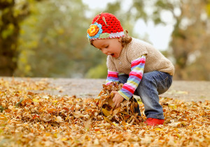 Cute child playing with autumn leafs